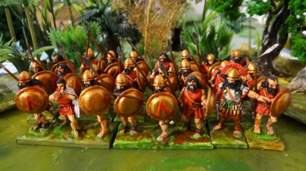 L'hoplite sans cuirasse équipé du casque dit de Pilos qui n'était pas métallique. habituellement le rouge est associé aux tuniques spartiates.