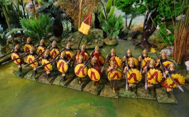 Figurines Minifigs. L'hoplite de 400 av JC est allégé, il est équipé d'une tunique de cuir. Il a toujours la coiffure spartiate avec cheveux longs et tresses.