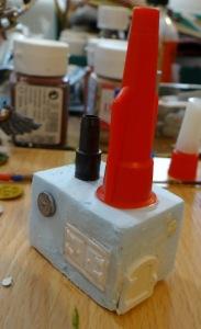 Le bloc moteur : une machine à vapeur à base de bouchons de colle, de petits boucliers et d'éléments Hirst art.